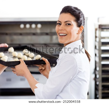 Side view portrait of happy female chef giving baking sheet to male colleague by oven in commercial kitchen - stock photo