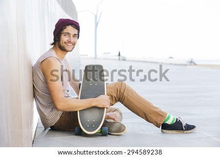 Side view portrait of happy man sitting with skateboard on footpath - stock photo