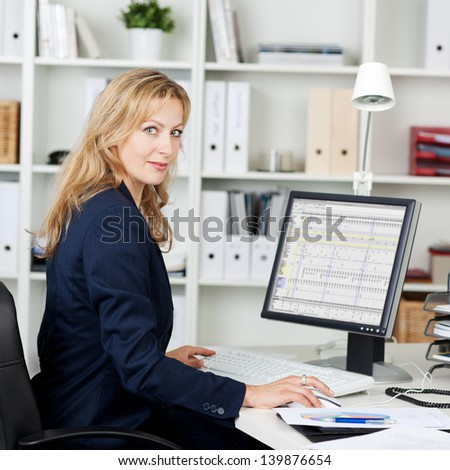 Side view portrait of mid adult businesswoman using computer at office desk - stock photo