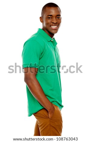 Side view portrait of smiling casual african guy posing with hands in pocket