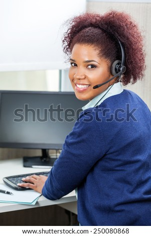 Side view portrait of smiling customer service representative using computer at desk in office - stock photo