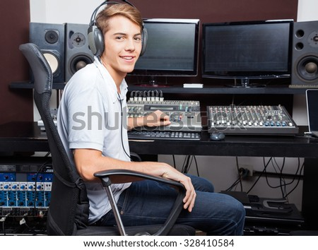 Side view portrait of smiling man mixing audio in recording studio - stock photo