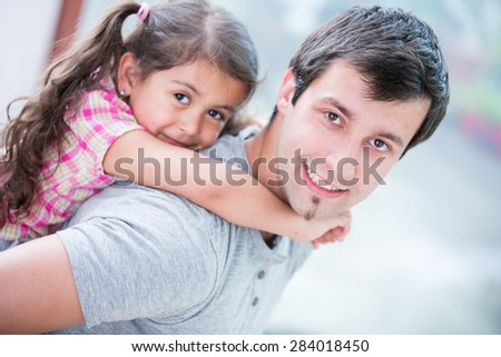 Side view portrait of smiling man piggybacking little daughter at home - stock photo
