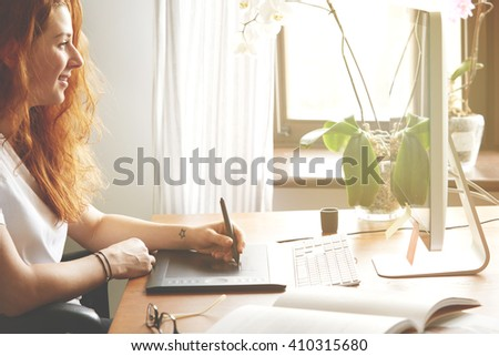 Side view portrait of smiling woman photographer working on the computer, hand drawing on graphic tablet. Young Caucasian redhead female retoucher editing photos at home. Flare sun, film effect  - stock photo
