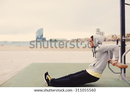 Side view portrait of strong man doing muscles exercises on training apparatus outdoors, fit man pumps biceps at seashore horizontal bar, sportsman at physical activity in cloudy cold morning, filter - stock photo