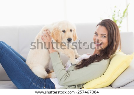 Side view portrait of young woman playing with puppy while lying on sofa at home
