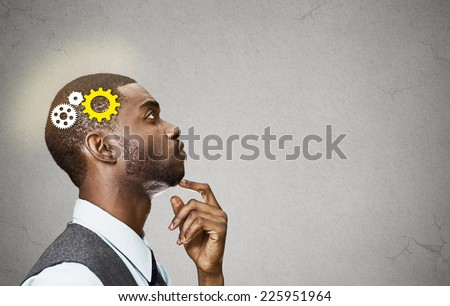 Side view portrait young business man thinking deciding finger on chin looking up gear mechanism over head isolated grey wall background copy space. Emotion facial expression perception intelligence  - stock photo