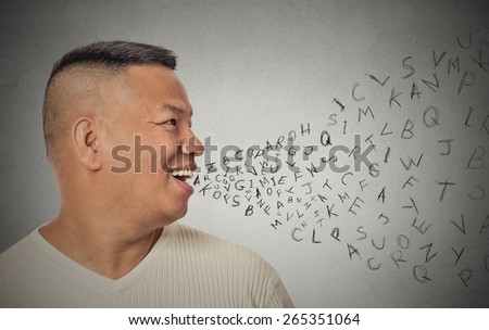 Side view portrait young handsome man talking with alphabet letters coming out of open mouth isolated grey wall background. Human face expression emotion perception. Communication concept - stock photo