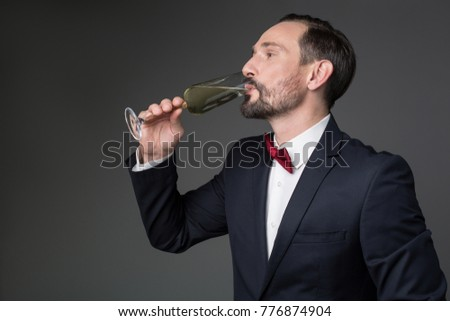 Side view profile of confident man tasting sparkling wine from glass. He is standing in formal suit. Isolated and copy space