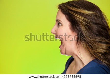 Side view profile portrait beautiful angry woman screaming wide open mouth isolated on green background. Negative human emotions, face expression, feelings, anger management problems  - stock photo