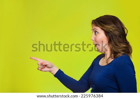 Side view profile portrait excited casual female pointing out at copy space isolated over green background. Human face expression, emotion, reaction, feeling - stock photo