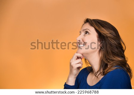 Side view profile portrait thoughtful happy woman smiling looking up daydreaming isolated over orange background. Positive human face expressions, emotions, feelings, perception  - stock photo