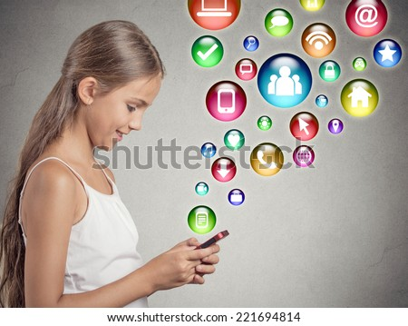 side view profile teenager girl using texting playing on smartphone with social media mobile phone application symbols icons coming flying out of cellphone isolated grey wall background. data plan - stock photo