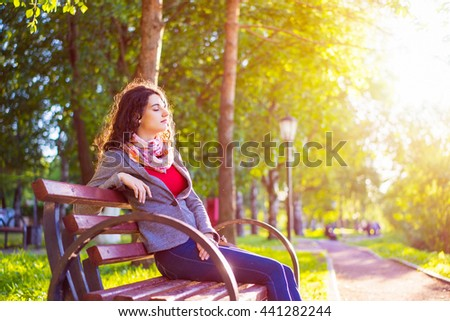 Side view seated brunette woman on the bench enjoying nature in sunny day outdoors, charming young girl relaxing in the summer park. Warm toned photo filter with blurred lens flare on background. - stock photo