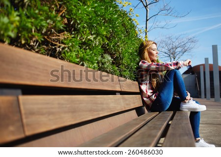 Side view seated woman on the bench enjoying nature in sunny day outdoors, charming young girl relaxing in the spring park, female student relaxing at campus during her class break - stock photo