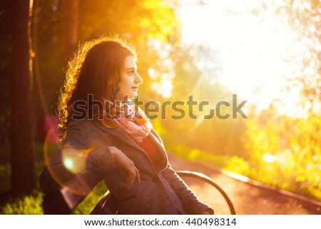 Side view seated woman on the bench enjoying nature in sunny day outdoors, charming young girl relaxing in the summer park. Warm toned photo filter with blurred lens flare on background.  - stock photo