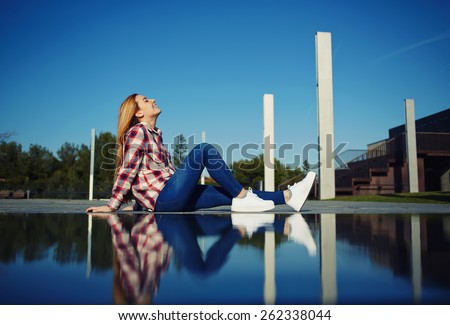 Side view shot of a young woman sitting in the park and enjoying the sunshine feeling so happy,relaxing girl enjoy outdoors with closed eyes, girl sitting next to the water with reflection of her self - stock photo