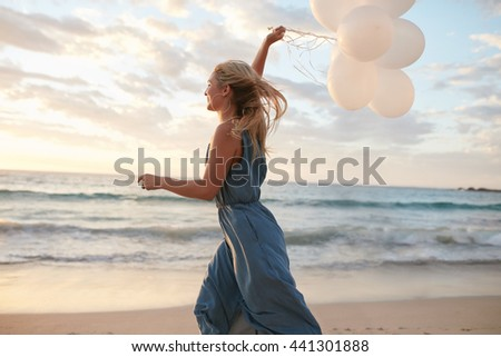 Side view shot of beautiful young woman running on the beach holding balloons. Female running on the sea shore and having fun. - stock photo