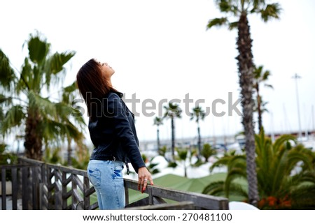 Side view shot of brunette young woman breathing fresh air and enjoying the view just arrived to hotel, attractive female enjoying the view while standing on the balcony during her vacation holidays - stock photo