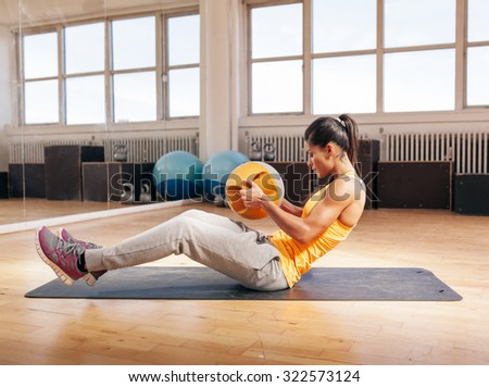 Side view shot of muscular young woman doing crossfit workout using kettlebell. Fitness model exercising in gym. - stock photo