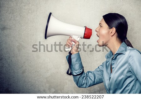 Side View Shot of Young Woman in Long Sleeves Silk Shirt, Shouting with Megaphone on an Abstract Background.