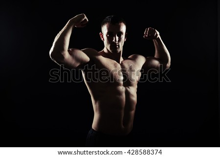 Side view silhouette of hot athletic young man showing muscles on dark background