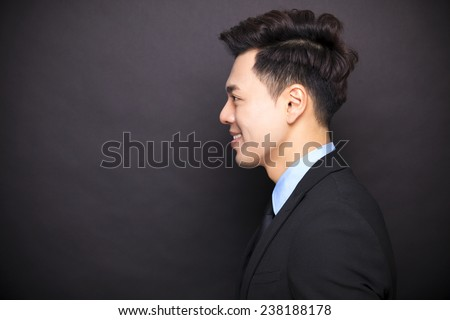side view smiling businessman standing before black background - stock photo