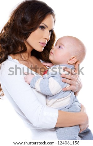 Side view studio portrait of a beautiful young mother cradling her little baby to her chest isolated on white