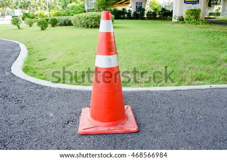 side view traffic cone on asphalt road park and under expressway background