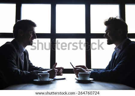 Side view. Two young businessmen working during a business lunch.