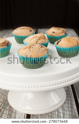 side view white cake stand with fresh homemade blueberry whole wheat muffins - stock photo
