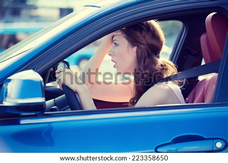 Side view window portrait displeased stressed angry pissed off woman driving car annoyed by heavy traffic isolated street background. Emotional intelligence concept. Negative human face expression - stock photo