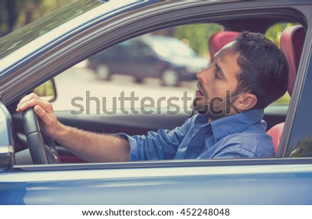 Side view window sleepy tired fatigued exhausted young man driving his car in traffic after long hour drive. Transportation safety sleep deprivation accident concept  - stock photo