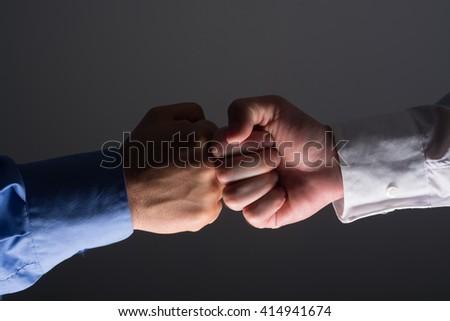 Side view with light source from below of fist bump handshake between businessmen over dark gray background - stock photo