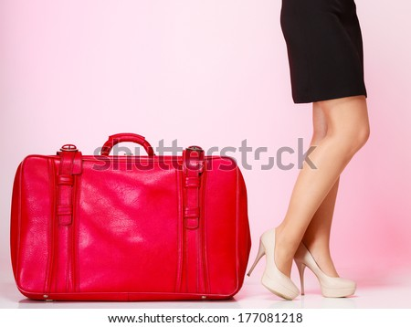 Side view woman legs high heels with old red suitcase on pink background. Elegant lady in voyage, travel concept.