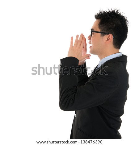 Side view young Asian business man shouting with hands cupped to his mouth, isolated on white background - stock photo