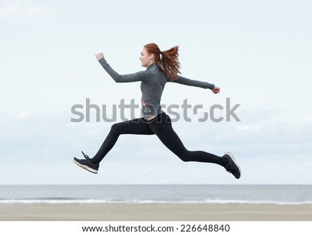 Side view young woman running and jumping outdoors