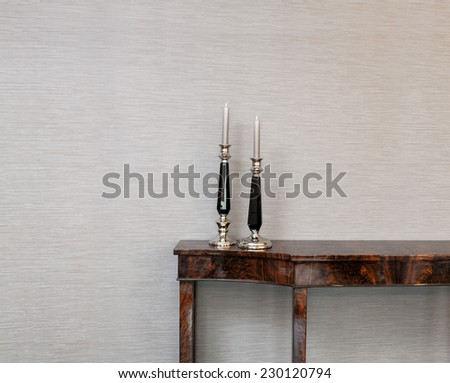Sideboard in front of a grey wall with candle stick - stock photo