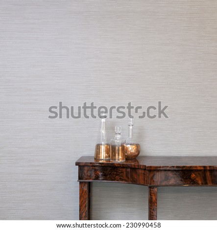 Sideboard in front of a grey wall with spirit bottle - stock photo
