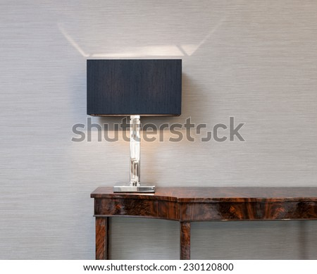 Sideboard in front of a grey wall with table lamp  - stock photo