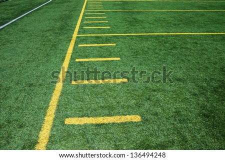 Sideline on American Football artificial turf field with hash marks.