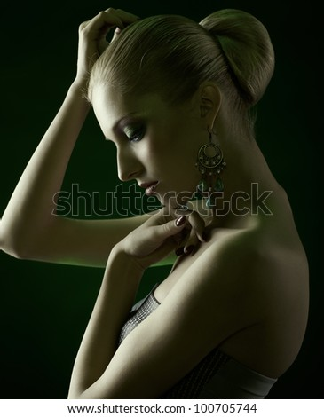 sideview green toned portrait of beautiful young blonde woman in jewellery - stock photo