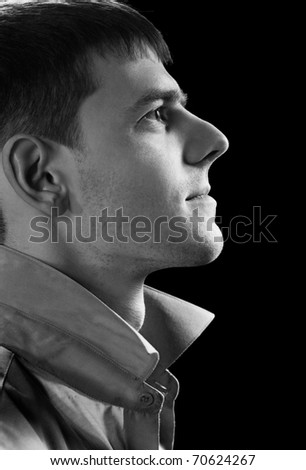 sideview headshot portrait of young handsome brunet guy posing in gray shirt on green