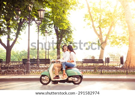 Sideview of a trendy couple riding a scooter in the morning. Sun is shining through trees - stock photo