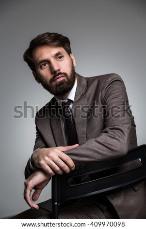 Sideview of businessman sitting on chair with elbow placed on chair back - stock photo