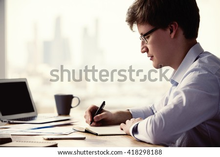 Sideview of caucasian businessman writing something in notepad placed on wooden office desk with laptop, smartphone, coffee and other items - stock photo
