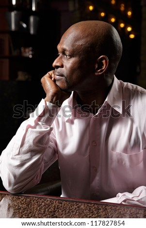 Sideview portrait of african man in pink shirt sitting at desk ornated with coffee beans - stock photo