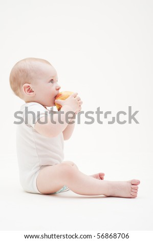 sideview portrait of baby with yellow apple