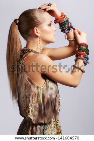 sideview portrait of beautiful young brunette woman in ear-rings and bracelets on gray - stock photo