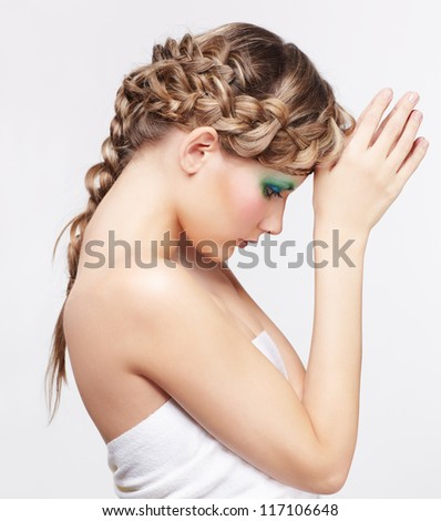 sideview portrait of beautiful young dark blonde woman with creative plait hairdo posing on gray